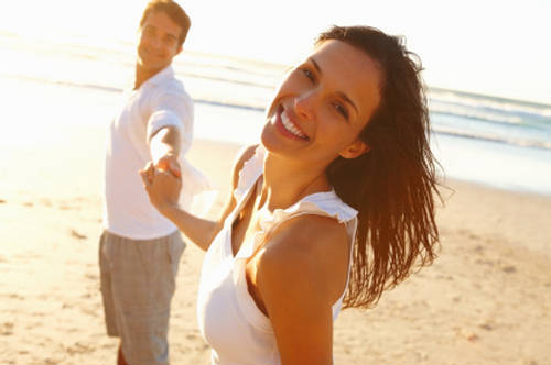 Woman smiling while holding hands with partner on beach